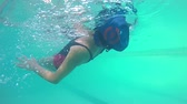 slomo : Female swimmer in rubber cap training back swimming in swimming pool, underwater view, SLOW MOTION