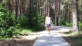 slomo : Runner woman running in forest park exercising outdoors, SLOW MOTION