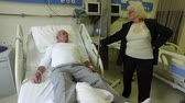 transfuse : Senior woman makes men patient hospital bed position adjustment