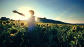 Rancher girl have fun in sunflower field walking against sunset