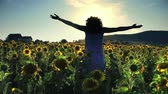 Beauty farmer girl in sunflower harvest. field at sunset. Hands open, freedom happiness concept