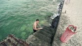 gezinmek : Handsome sport fit boy come out of sea water on port stairs, SLOW MOTIION