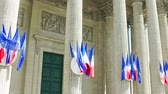 Row of French flags waving on columns of Pantheon in Paris