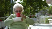 elderly old woman with injured hand drinking coffee outdoor sitting Wideo