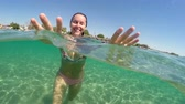 pływak : Underwater view happy diving teen girl with long hair smiling and kissing the camera