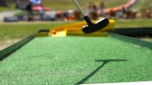 golfing : Playing mini golf, cinematic view. Golf ball and Golf Club on Artificial Grass Stock Footage