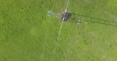 condutor : High voltage tower from above, green meadow background