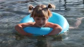 Pretty little girl swimming with inflatable circle