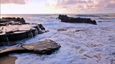 гавайский : waves breaking on rocks after sunrise close to Sandy beach, Oahu, Hawaii Стоковые видеозаписи