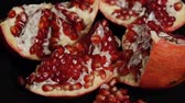 Delicious pomegranate. Portion of fresh made pomegranate. Fresh red pomegranate seeds isolated on a black background.