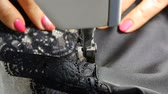 Closeup of tailor. Female hands of a seamstress at work. Sewing with a sewing machine with black material. Black lace. Factory textile sewing. Fashion industry.