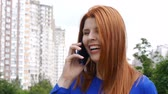 Young beautiful girl with red hair in the city, dials a phone number, talking on a mobile phone and smiling.