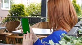 Girl with red hair sitting in cozy cafe. Using mobile phone with green screen.