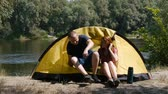 Concept of tourism and travel. Young happy couple sitting in tent watching the view. The beautiful nature surrounds young people. Drinking a tea. Forest and river on the background. Стоковые видеозаписи