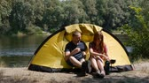 Content happy couple sitting in tent. Concept of tourism and travel. The girl pours tea from a flusk. Forest and river on the background.