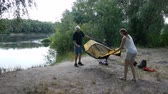 Father and daughter putting up tent, preparing to overnight in wild, green tourism, hiking. Happy travels concept.