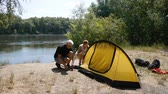 Father and daughter campers putting up tent. Happy travels concept, green tourism, hiking.