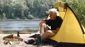 Hiker sitting in a tent. Camper man drinking coffee or tea. River and forest in the background. Relaxation, travel, green tourism concept. Стоковые видеозаписи
