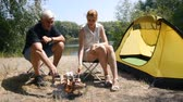 A man and a girl roasting marshmallows on a fire. Marshmallow ready. Hiking, travel, green tourism concept. Healthy active lifestyle. River and forest in the background. Стоковые видеозаписи
