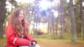 jacket : Beautiful smiling little girl with long hair in a red jacket on background of the autumn city park.