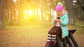 jacket : Beautiful smiling little girl in a blue jacket and a red cap with a mobile phone on the background of the autumn city park.
