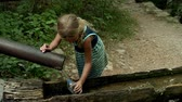 tubos : Little beautiful girl is drinking water from a spring in the Great Paklenica, Croatia.