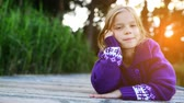 Little beautiful girl lies on the river pier and smiling. Stock Footage