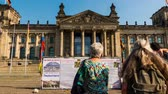 обращается : BERLIN, GERMANY - SEPTEMBER November 2016: timelapse of rally to ask for help about Reichstag building (Bundestag) is a historical edifice, constructed to house the Imperial Diet of the German Empire.