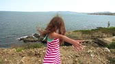 light : Little beautiful girl on rocky shore of Mediterranean Sea.