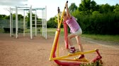 fitness : Little beautiful girl engaged in sports training apparatus in the summer city park.