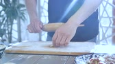 nutritious : cook rolls dough circles for patty with rolling-pin on wooden board in kitchen at bright daylight from window