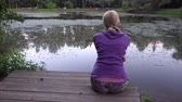 solitário : Young woman sitting by the pond 4k