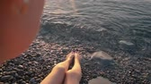 pedicure : Female legs barefoot on shore at sunrise Stock Footage
