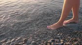 педикюр : Female feet standing and walking barefoot on shore at sunrise