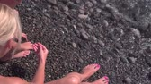 Young slim mother and her son play with pebbles on beach Dostupné videozáznamy