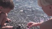Young slim mother and her son play with pebbles on beach, slow motion Dostupné videozáznamy