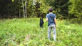 Boy and black dog playing with stick together in the nature in summer