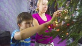 Mother and kid decorating Christmas tree by hanging balls and garland on its branches