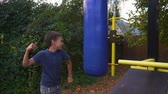 Boy beating a punching bag. Slow motion Dostupné videozáznamy