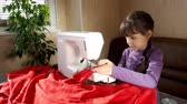 pomáhá : The child learns to sew on the sewing machine.