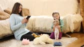 tot : Mom with a child playing with a doll beside the couch Stock Footage