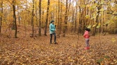 game : mother with her baby in autumn forest throwing leaves