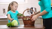 preparation : girl helps her mother pulling vegetables from the basket