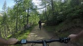 POV man riding e-bike following friend woman.Mtb action cyclist exploring together trail path near forest.Electrical bike active people sport travel vacation in Italy Alps outdoors in summer.4k video