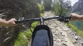 cyklista : POV man riding e-bike on rocky trail near lake.Mtb action cyclist exploring path near mountains.Electrical bike active people sport travel vacation in Europe Italy Alps outdoors in summer.4k video