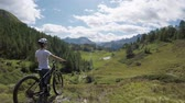 POV forward on hills and forest woods with mountain cyclist woman looking landscape panorama with mtb e-bike in summer outdoors.Wanderlust active sport travel people.Alps wild nature.4k drone video