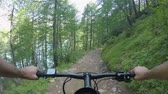pov : POV man riding e-bike along lake.Mtb action cyclist exploring trail path near mountain forest woods.Electrical bike active people sport travel vacation in Europe Italy Alps outdoors in summer.4k video