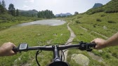 POV man riding e-bike on hill near lake.Mtb action cyclist exploring trail path near mountains.Electrical bike active people sport travel vacation in Europe Italy Alps outdoors in summer.4k video