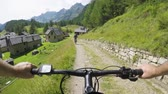 POV man riding e-bike to town village.Mtb action cyclist exploring path near mountains.Electrical bike active people sport travel vacation in Europe Italy Alps outdoors in summer.4k video