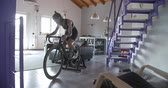 young tattooed cyclist woman cycling with bicycle at home fitness sport workout .Living room domestic training. 4k slow motion video Stok Video